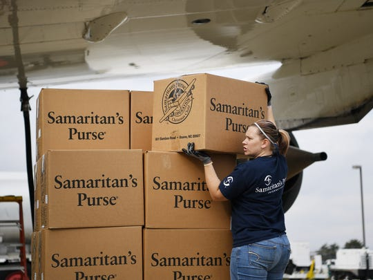 Erica Vestal helps to load Operation Christmas Child boxes onto a Samaritan's Purse airplane at Piedmont Triad International Airport in Greensboro, North Carolina, November 6, 2017.