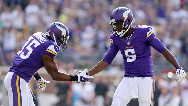 Minnesota Vikings quarterback Teddy Bridgewater (5) celebrates a touchdown with wide receiver Greg Jennings (15) during the first quarter against the Atlanta Falcons at TCF Bank Stadium.