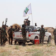 Iraqi security forces and Shiite militiamen chant anti-terrorism slogans after breaking the siege on 15,000 Shiite Turkmens stranded in the farming community town of Amirli, following U.S. airstrikes against Sunni Islamic State group positions, 105 miles north of Baghdad, Sunday, Aug. 31, 2014.