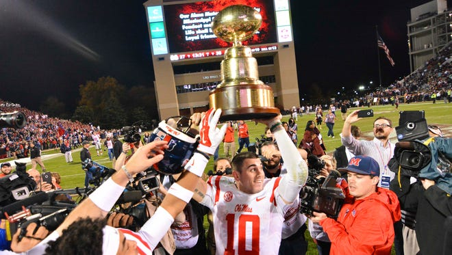 Ole Miss quarterback Chad Kelly holds the Egg Bowl trophy after another strong performance Saturday night.