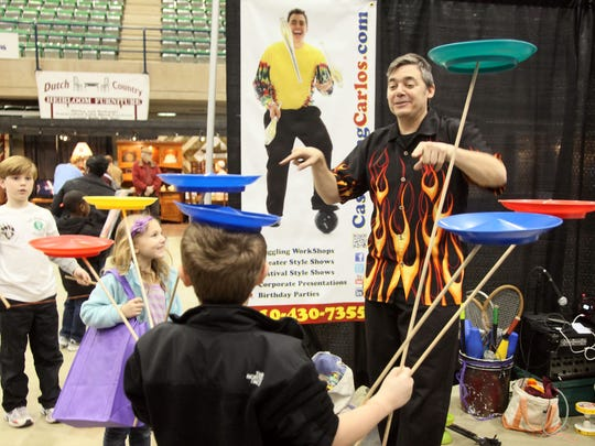 Juggler Carlos Mir shows children how to balance spinning