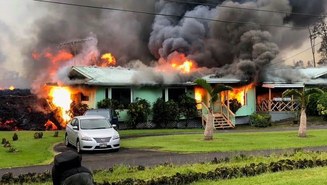 Lava engulfs a home in the Leilani Estates neighborhood of Hawaii on May 6, 2018.