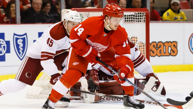 Detroit Red Wings center Gustav Nyquist (14) skates with the puck in front of Arizona Coyotes goalie Mike Smith (41) and defenseman Andrew Campbell (45) in the first period at Joe Louis Arena.