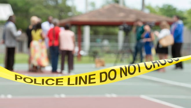 Police tape remains around the Fricker Community Center basketball courts after an overnight shooting, as local civil rights activists call for a unified stance against gun violence during a press conference at the center in Pensacola on Thursday, May 17, 2018.