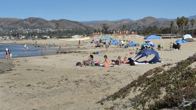 Visitors cool off at Ventura Harbor Cove Beach on Monday, as temperatures climbed.