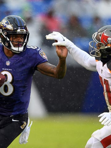 Baltimore Ravens quarterback Lamar Jackson, left, rushes against Tampa Bay Buccaneers free safety Jordan Whitehead in the first half of an NFL football game, Sunday, Dec. 16, 2018, in Baltimore. (AP Photo/Nick Wass)
