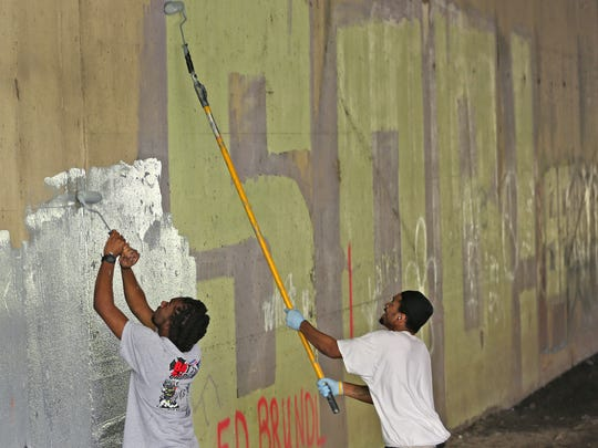 Kelsey Robinson, left, and Romello Maxwell, with the Indianapolis Graffiti Abatement Unit, paint over graffiti at an overpass along Fall Creek on the Fall Creek Greenway, Tuesday, Sept. 26, 2017.