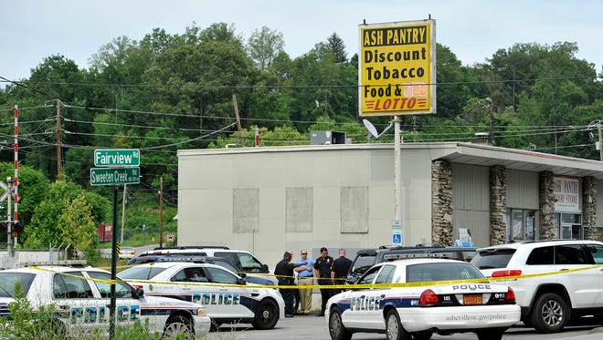 Officials investigate the scene of a shooting at Ash Pantry Food Store at the corner of Sweeten Creek and Fairview Roads on Thursday.