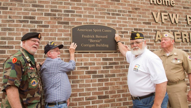 Positioning a plaque Thursday, May 25, 2017 that will be unveiled on Memorial Day at the American Spirit Centre are, from left, Dick Young, co-captain of the VFW honor guard, quartermaster Ralph Schlaff, American Legion commander Mike Omstead and Am. Vet. commander Tim Maher.