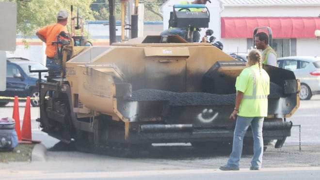 Eppel Construction employees work on blacktopping the County Market parking lot Tuesday morning.