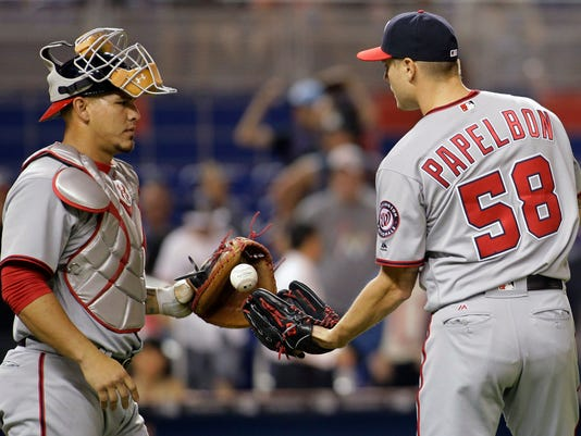 Washington Nationals catcher Wilson Ramos, left, gives the ball to pitcher Jonathan Papelbon (58) after the Nationals defeated the Miami Marlins 3-1 during a baseball game Wednesday, April 20, 2016, in Miami. (AP Photo/Luis M. Alvarez)
