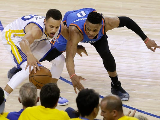 Golden State Warriors guard Stephen Curry, left, is defended by Oklahoma City Thunder guard Russell Westbrook during the second half of Game 1 of the NBA basketball Western Conference finals in Oakland, Calif., Monday, May 16, 2016. The Thunder won 108-102. (AP Photo/Jeff Chiu)