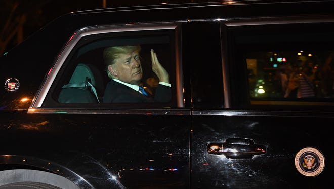 President Trump waves upon his arrival to his hotel in Singapore on Sunday ahead of a planned meeting with North Korea's leader.