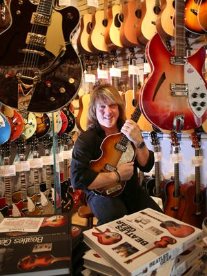 Andy Babiuk in his guitar store, Andy Babiuk's Fab Gear, in Fairport Wednesday, Dec. 9, 2015.  Babiuk is holding a Hofner 500/1 Vintage '62 Bass, first made popular by Paul McCartney.