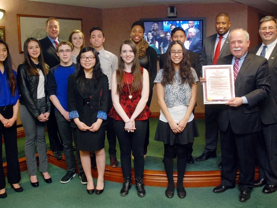Union County Freeholder Chairman Mohamed Jalloh (third from right) and Freeholders Bruce Bergen (third from left) and Alexander Mirabella (right) present a resolution to Union County Vocational-Technical Schools Superintendent Peter Capodice (second from right) and students from the Scotch Plains-based school designating February 2015 as National Career and Technical Education Month in Union County.