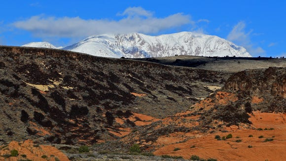 The snow-covered Pine Valley Mountains loom in the distance beyond Snow Canyon State Park.