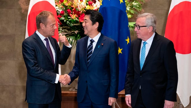 Japanese Prime Minister Shinzo Abe, center, shakes hands with European Council President Donald Tusk next to European Commission President Jean-Claude Juncker, right, before a meeting at Abe's official residence in Tokyo Tuesday, July 17, 2018.