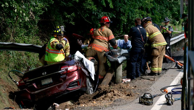 Firefighters carry a man from a crashed car Wednesday, June 27, 2018, in the 1400 block of Ohio 158 in Greenfield Township. Two people were taken to Grant Medical Center in Columbus after being cut from the car which came to rest in a ditch on the east side of the highway. Law enforcement officers were looking for another vehicle that might have been involved in the crash. No description of the other vehicle of its driver were immediately available.