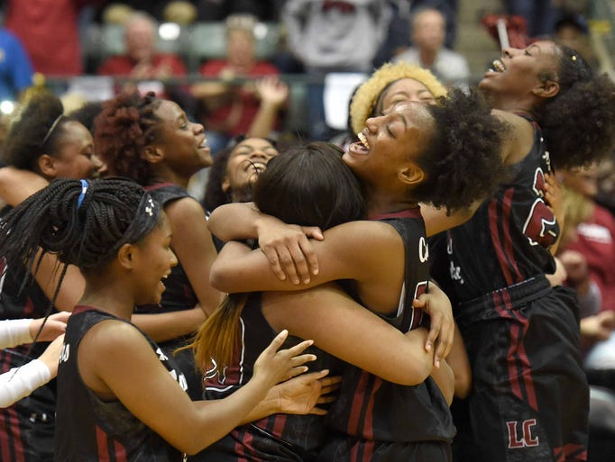 The Lawrence County Lady Cougars celebrate after beating