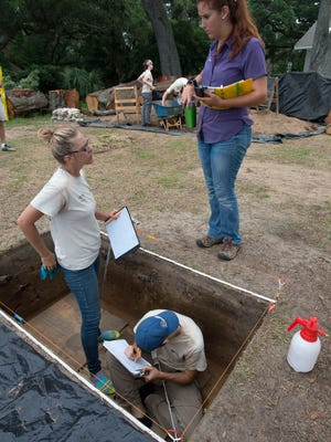 University of West Florida student Cathryne Miller, center, reports her team's progress to graduate student Emma Dietrich, right, while Kaleb Farman, left, continues his work at the site of the deLuna settlement overlooking Escambia Bay.
