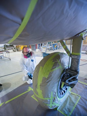 Mike Clouse paints the wheel of the replica of Jimmy Doolittle's WWII being worked on at the National Naval Aviation Museum in Pensacola on Wednesday, March 22, 2017.