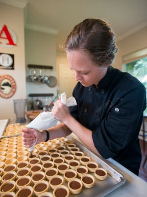 Justine Gudmundson-McCain makes salted caramel dark chocolate tarts at Bluejay's Bakery in Pensacola on Tuesday, May 23, 2017.