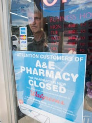 A&E Pharmacy co-owner David Enfinger hangs a notice