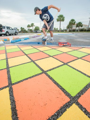 Senior Jordan Pliska paints his parking spot at Gulf