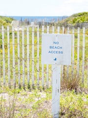 """Signs noting """"No Beach Access"""" in a subdivision off"""
