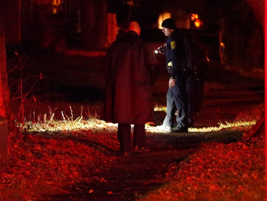 Police search the area where a man was shot Thursday