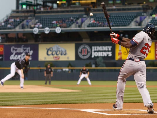 Atlanta Braves' Cameron Maybin, front, singles on a pitch from Colorado Rockies' Kyle Kendrick during the first inning of a baseball game Thursday, July 9, 2015, in Denver. (AP Photo/David Zalubowski)