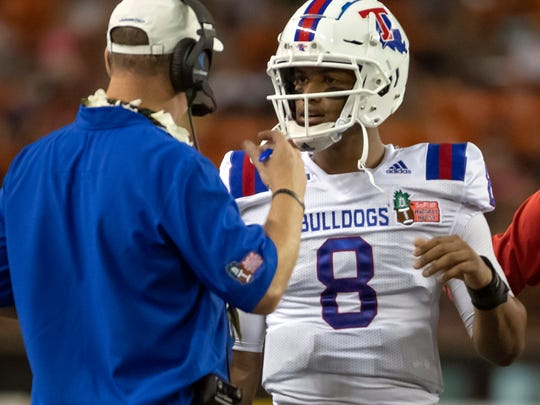 Louisiana Tech head coach Skip Holtz, left, talks to quarterback J'Mar Smith (8) during a timeout in the first half of the Hawaii Bowl NCAA college football game against Hawaii, Saturday, Dec. 22, 2018, in Honolulu. (AP Photo/Eugene Tanner)