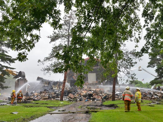 Firefighters from St. Cloud and several other departments continue Sunday morning to fight an overnight fire that destroyed the Roosevelt Education Center at 3015-3rd Street North in St. Cloud.