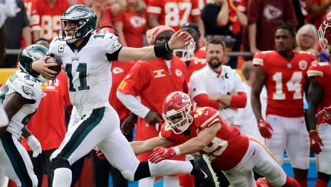 Philadelphia Eagles quarterback Carson Wentz (11) runs past Kansas City Chiefs defensive back Daniel Sorensen (49) during the second half of an NFL football game in Kansas City, Mo., Sunday, Sept. 17, 2017.