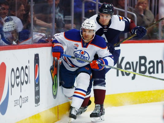 Edmonton Oilers defenseman Andrej Sekera, front, of Slovakia, is run into the boards by Colorado Avalanche center Joe Colborne as they pursue the puck in the first period of an NHL hockey game Thursday, March 23, 2017, in Denver. (AP Photo/David Zalubowski)