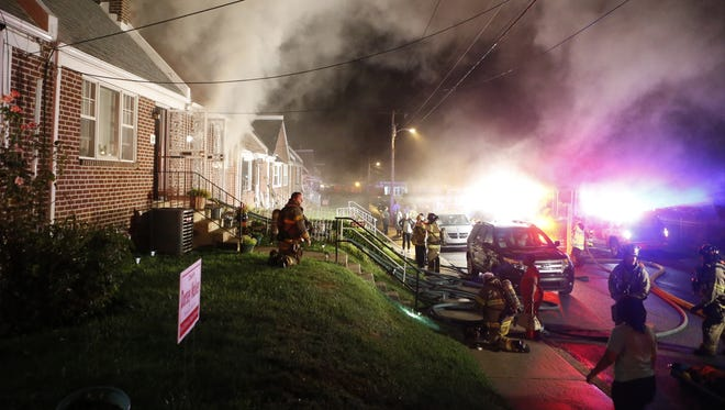 Wilmington firefighters work at the scene of a house fire in the 1300 block of E. 23rd Street, reported about 8:30 p.m. Saturday, August 23, 2014.