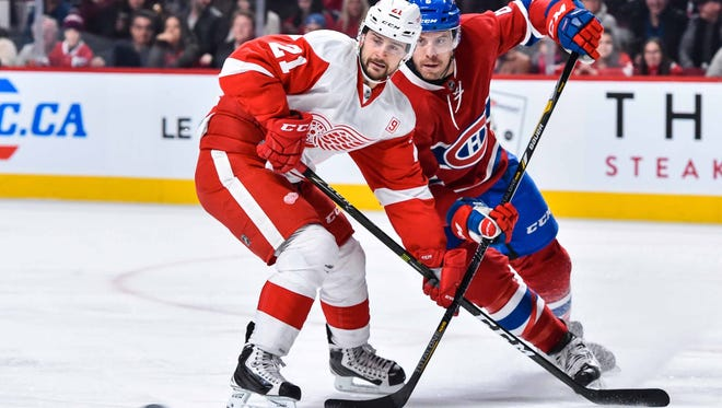 Tomas Tatar of the Detroit Red Wings and Shea Weber of the Montreal Canadiens skate after the puck.
