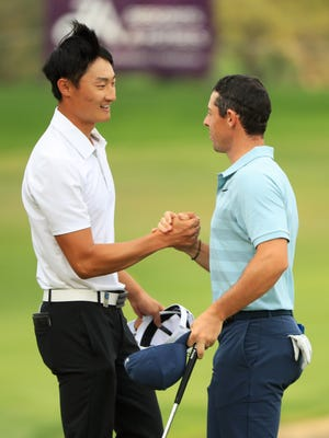 Haotong Li (left) shakes hands with Rory McIlroy as he celebrates his  victory at the Dubai Desert Classic.