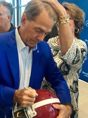 Nick Saban's wife Terry fixes his hair while he autographs