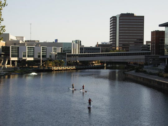 People try stand-up paddleboarding September 16, 2015, on the Grand River in downtown Lansing. [MATTHEW DAE SMITH | for the Lansing State Journal]