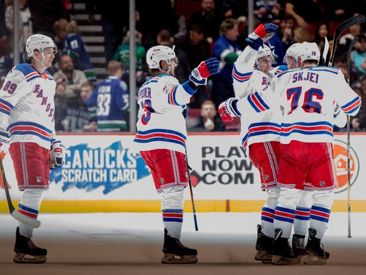 New York Rangers' Pavel Buchnevich, Ryan Spooner, John Gilmour, Vladislav Namestnikov and Brady Skjei, from left, celebrate Gilmour's overtime goal against the Vancouver Canucks during an NHL hockey game Wednesday, Feb. 28, 2018, in Vancouver, British Columbia. (Darryl Dyck/The Canadian Press via AP)