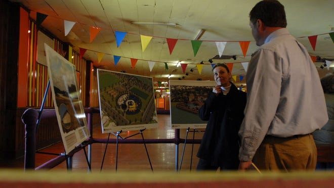 Terri Rose speaks with Chris Carbaugh as she looks over plans for the Atlantic Town Center development at the Dream Roller Rink in Wattsville at an open house in 2010.