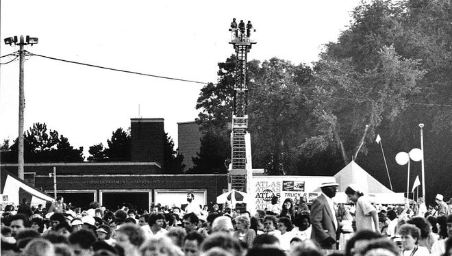 East Lansing firefighters from Station #2 get a birds eye view of the crowd at the Smokey Robinson concert, Aug. 14, 1990 at the Michigan Festival.