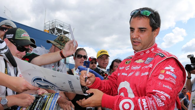 Juan Pablo Montoya signs autographs during qualifications for the NASCAR Sprint Cup Series auto race at Michigan International Speedway in Brooklyn, Mich., Friday, Aug. 16, 2013.