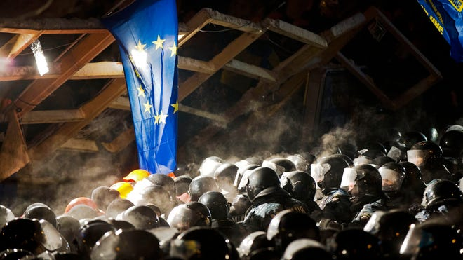 An EU flag hangs from barricades as Ukrainian riot police storm pro-European Union activists' tent camp in  Independence Square in Kiev on Dec. 11.