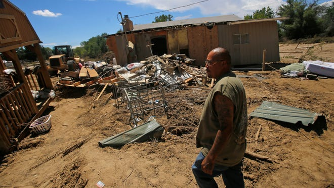 Eric Shorty on Monday walks as he talks about the damages done to his relative's home located next door to the Shorty residence on Farm Road in Shiprock.