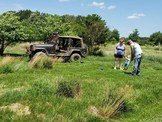 Three golfers take part in the Deer Run Jeep Golf course.