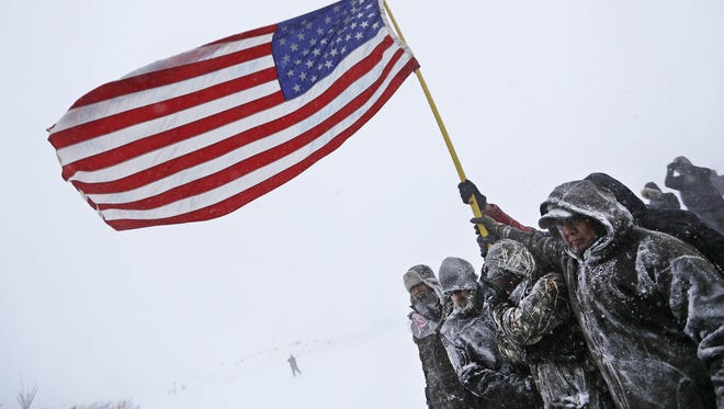 Military veterans huddle together to hold an American flag against strong winds during a march to a closed bridge outside the Oceti Sakowin camp where people have gathered to protest the Dakota Access oil pipeline in Cannon Ball, N.D., on Monday.