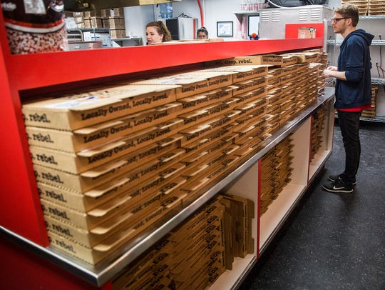 Employees work behind the counter at HotBox Pizza Wednesday.