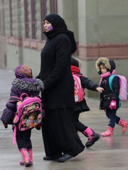 A Muslim woman walks with children at the end of a
